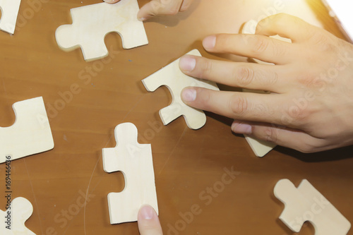 Fototapety, obrazy: Business partnership or teamwork concept with a business people presenting a matching puzzle piece as they cooperate on finding an answer and solution, close up of their hands.