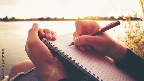 Foto  Close up hand of young woman with pen writing on notebook at riverside in the evening