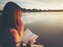 Young Woman Reading The Book At Riverside In The Evening.