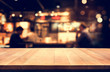 Wood table top with blur light bokeh in night cafe background .Lifestyle and celebration concept