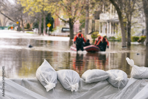 Fototapeta Flood Protection Sandbags with flooded homes in the background (Montage)