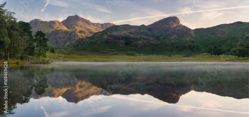 Fotobehang Meer / Vijver Calm morning with lake mist and reflections at Blea Tarn in the Lake District, UK.