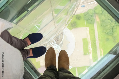 Fényképezés  Male and female feet on a glass floor at the Ostankino tower in Moscow, Russia