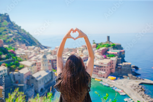 Beautiful girl making with hands heart shape on the old coastal town background Canvas