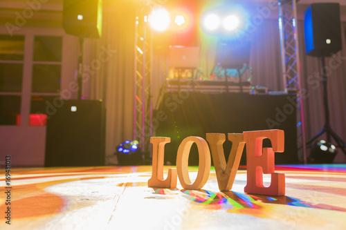 Photo  Hölzerndes Schild Love auf einer Tanzfläche von einem DJ nach der Hochzeitsfei
