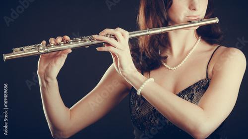 Obraz na PCV (fotoboard) Kobieta bawić się poprzecznego flet na czerni.