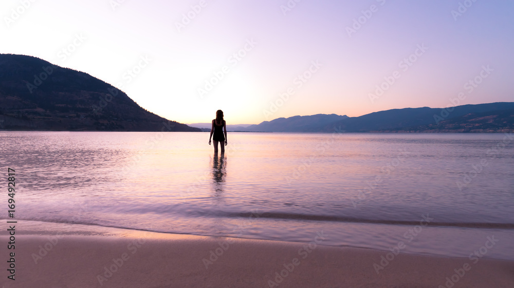 Fototapeta Silhouette of woman standing in Okanagan Lake at beach watching summer sunset with mountains in distance