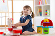 Child playing in nursery with educational toys. Toddler kid in a playroom. Little girl cooking in toy kitchen.