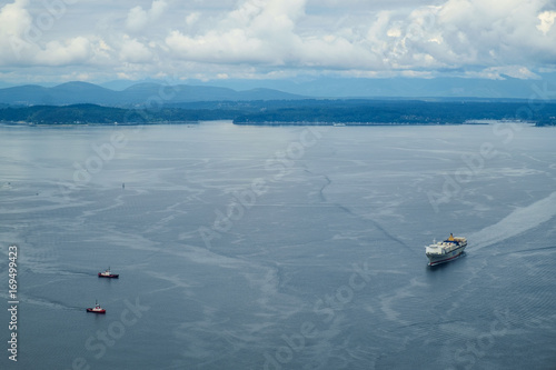 Tugboats coming to assist a container ship Poster