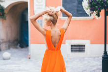 Back View Of Blonde Woman Model In Orange Dress Correctig Her Hair Outdoor In Antique Yard With Orange Old House.