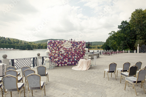 Poster Taupe Wedding altar made of wall of pink and violet flowers stands before the lake