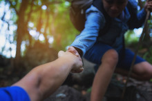 The Image Of A Tourist Helping With A Hand Pull While Climbing High.