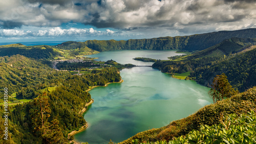 Photo Stands Olive Establishing shot of the Lagoa das Sete Cidades lake taken from Vista do Rei in the island of Sao Miguel, The Azores, Portugal. The Azores are a hidden gem holiday destination in Europe.