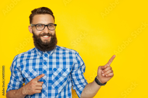 Fotografia  Cheerful hipster pointing on side