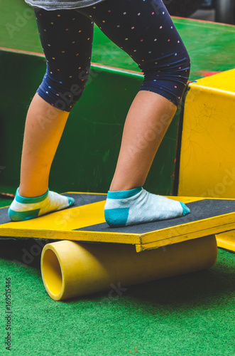 girl standing on a seesaw