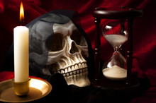 """Black Magic, Halloween And Memento Mori (latin For """"remember That You Have To Die"""") Concept With A Skull Representing Death, A Lit Candle And An Hourglass Symbolizing The Passing Of Time"""