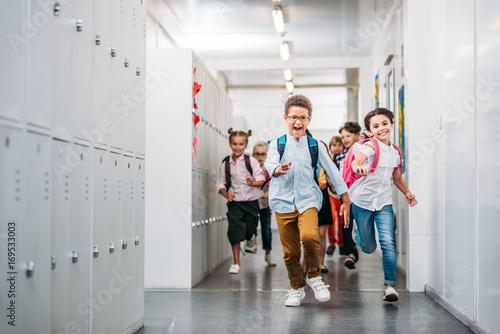 Plakat uczniowie biegający przez szkolny korytarz