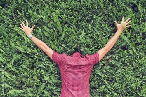 Fotografía  Faceless man hiding in a bush outdoors.
