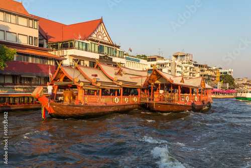 Ships at the pier for river cruise on a rice barge on the Chao Phraya river in Bangkok. Traditional rice barge, built for gastronomy on the river