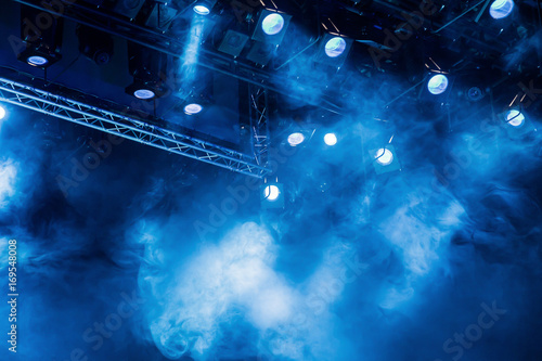 Blue light rays from the spotlight through the smoke at the theater or concert hall. Lighting equipment for a performance or show.