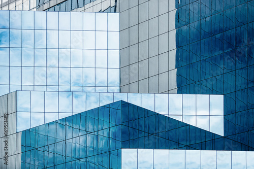 Blue sky and clouds reflecting in windows of modern office building Fototapet