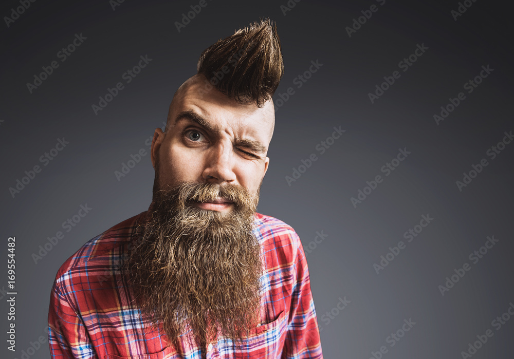 Fototapety, obrazy: Excited trendy man portrait. Punk styled man with Mohawk hairstyle is smiling. Isolated on gray background