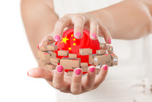 Two Woman Hands Protecting Sphere With China Flag Surrounded By Cardboard Boxes With Parcel Goods.