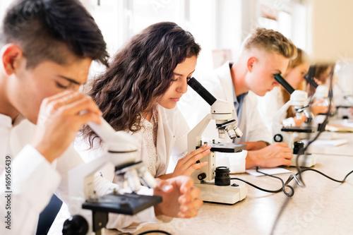 Fotografie, Obraz  Beautiful high school students with microscopes in laboratory.
