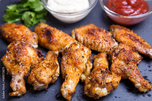 Chicken wings of a barbecue with two sauces on a black board. Close-up. Selective focus.