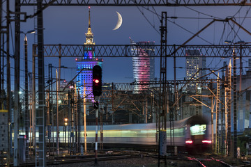 Partial moon over Warsaw city and train junction