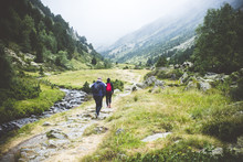 Couple Of Hikers Walking Throug A Valley Between Two Mountains