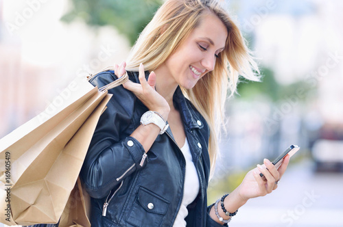 Fotografía  Young smiling woman with shopping bags read something in smartphone