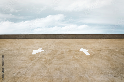 Traffic Arrows on a Parking Garage Rooftop with a Cloudy Sky Canvas Print