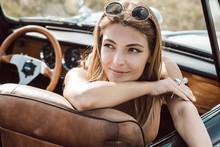 Young Woman Posing In Convertible Car
