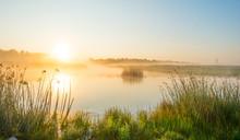 Shore Of A Misty Lake At Sunri...