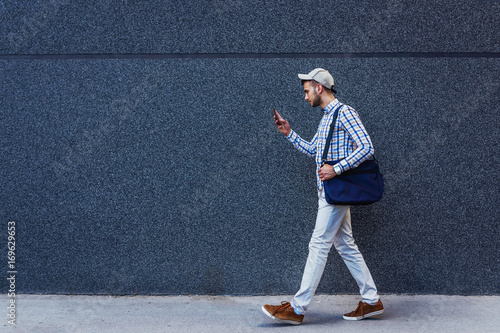Young urban casual businessman walking and reading messages on smartphone