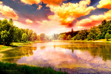 Mysterious Summer Nature Background With Blue Lake, Cloudy Sky, Inshore Forest And Spectacular Sunset Reflected In Water