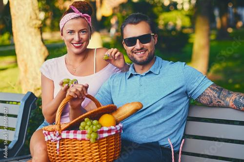 Zdjęcie XXL Para ma piknik na ławce w parku.