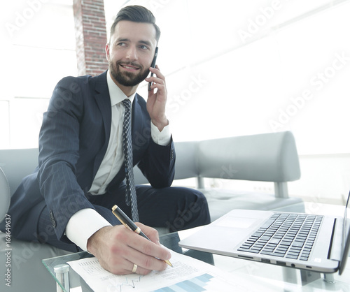 Garden Poster Businessman talking on smartphone about financial documents
