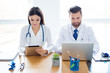 canvas print picture - Two doctors colleagues are sitting at the work place and using modern technology for their work, in white coats, focused