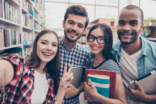 Selfie time! Four international students with beaming smiles are posing for selfie shot, caucasian attractive lady is taking, in school library building. Gathered, cheerful, smart and successful youth
