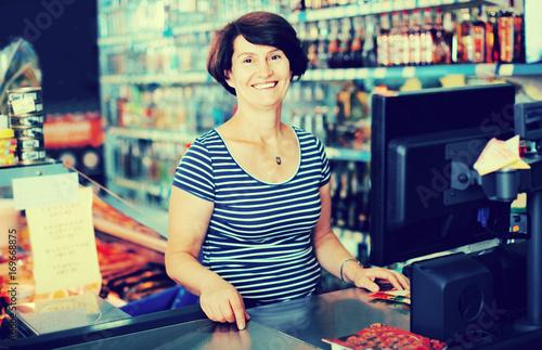 Spoed Foto op Canvas Muziekwinkel Portrait of an elderly woman near the cashdesk