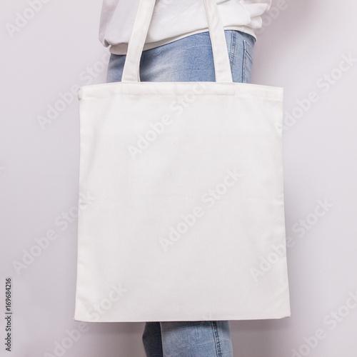 Fototapeta Girl in blue jeans holds blank cotton eco tote bag, design mockup. Handmade shopping bag for girls obraz