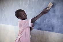 School Girl Cleaning Blackboard In Classroom