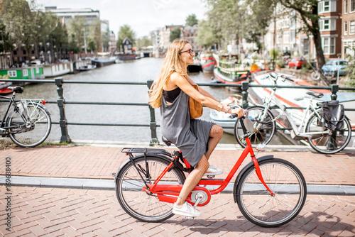 Fototapeta premium Młoda piękna kobieta, jazda na rowerze na moście nad kanałem wodnym w starym mieście w Amsterdamie