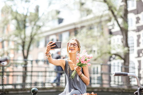 Photo  Young woman making selfie photo with bouquet of pink tulips sitting on the fence