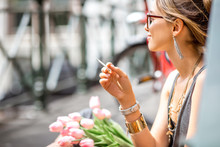 Young Beautiful Woman Smoking A Cigarette Sitting With Flowers In Amsterdam City