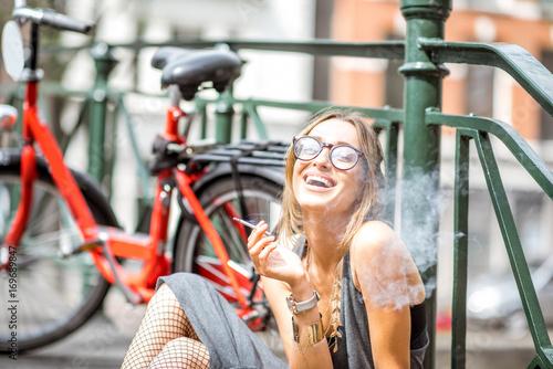 Fototapeta premium Młoda uśmiechnięta kobieta pali papierosa siedząc z kwiatami i rowerem na moście w mieście Amsterdam