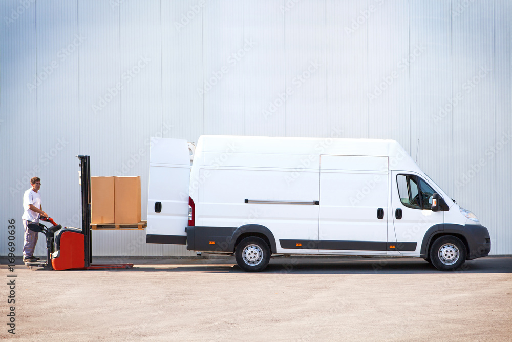 Fototapeta Courier is loading the van with parcels.