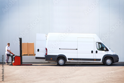 Fototapeta Courier is loading the van with parcels. obraz